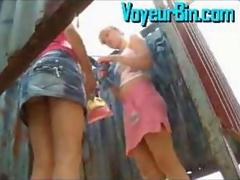 Two teens changing in their bikinis in a beach cabin