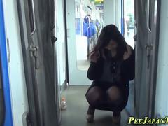 Asian peeing on train