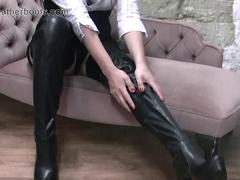 Sexy secretary babe slowly pulls on her leather thigh boots over her nylon stockings
