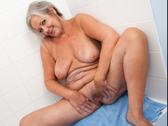 Granny is teasing on webcam and fingering her self in a bathroom